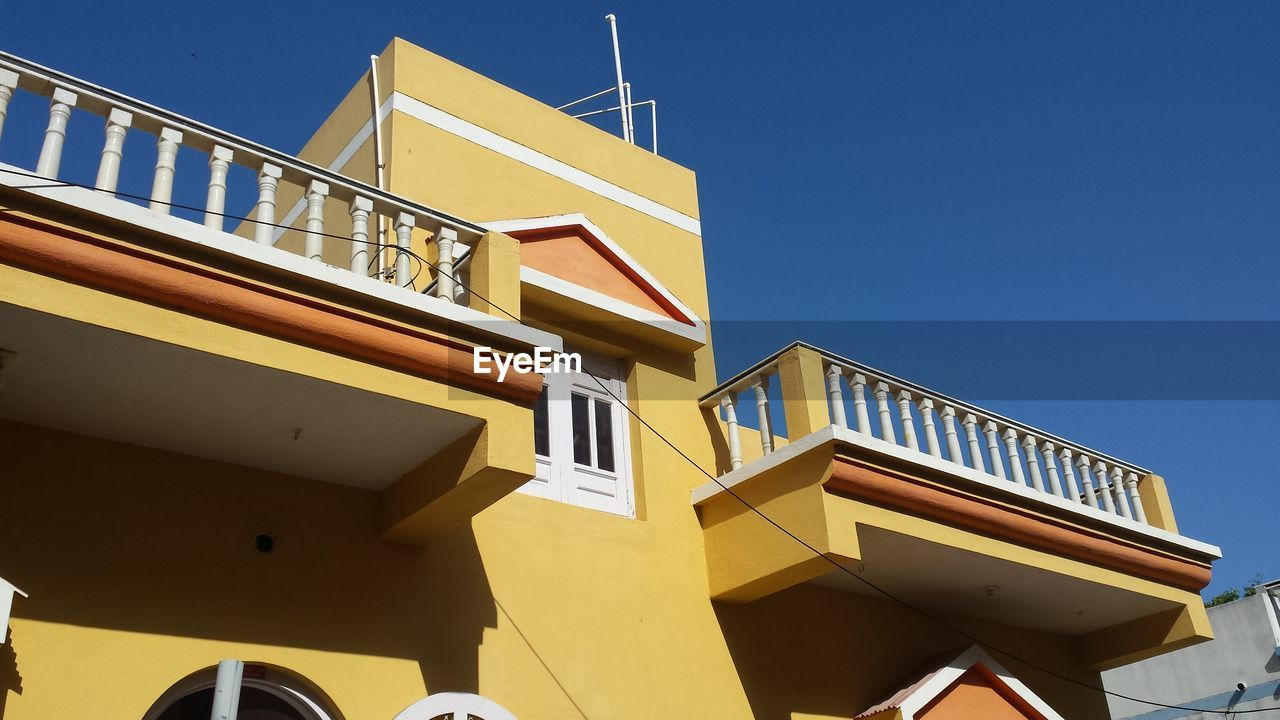 LOW ANGLE VIEW OF STEPS AGAINST YELLOW BLUE SKY