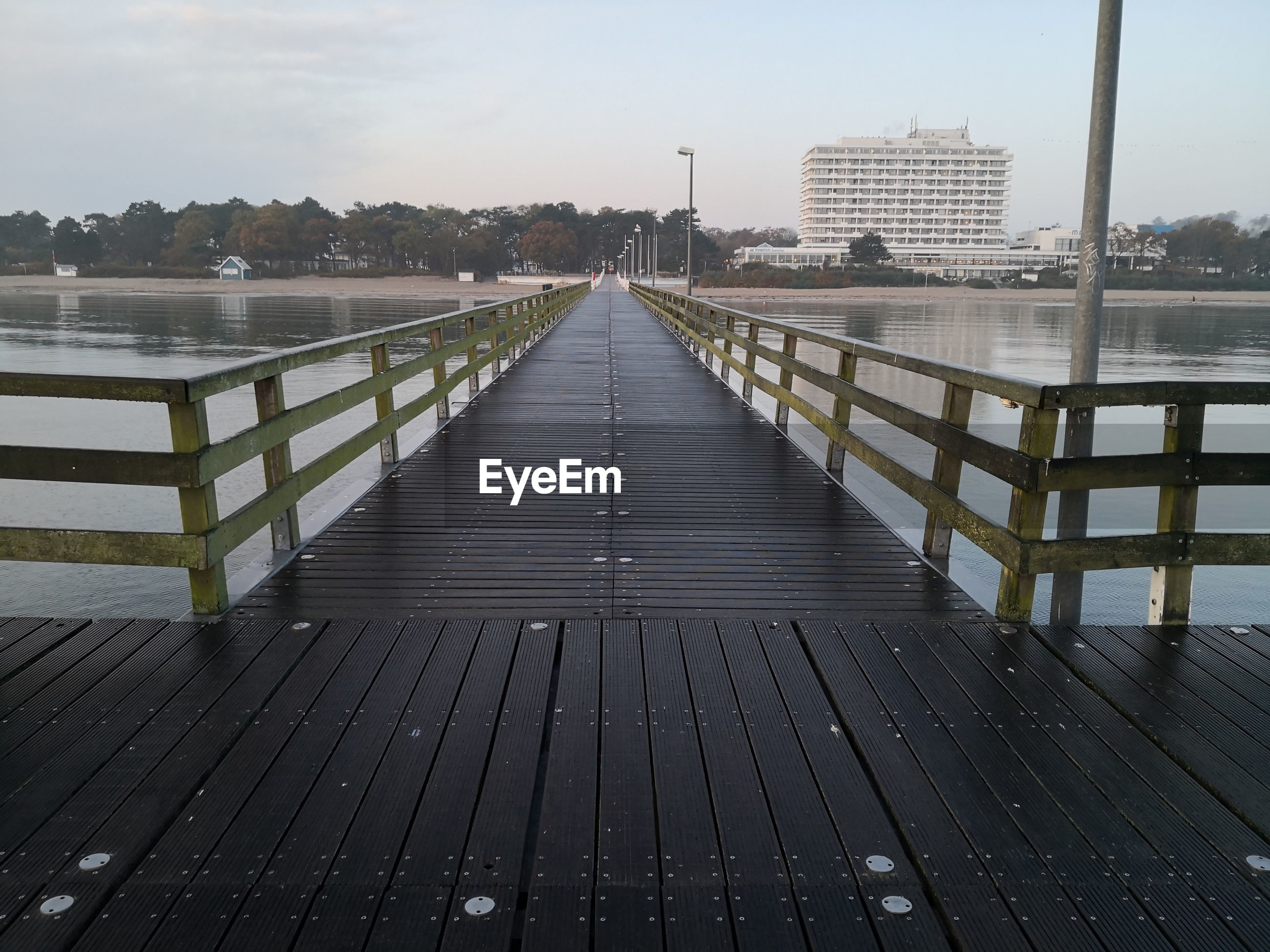 Pier over river in city against sky