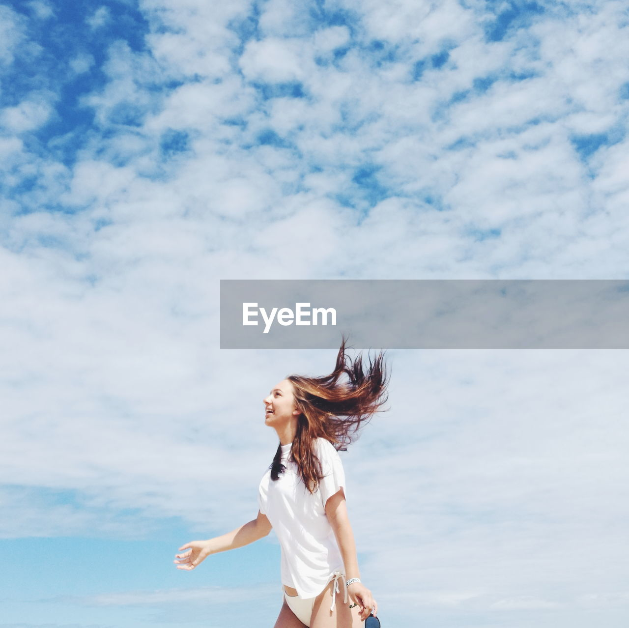 Smiling Young Woman Standing Against Cloudy Sky