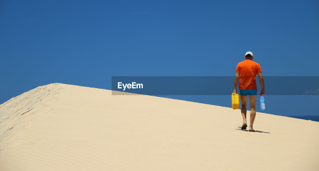 Rear View Of Man Standing On Sand Dune