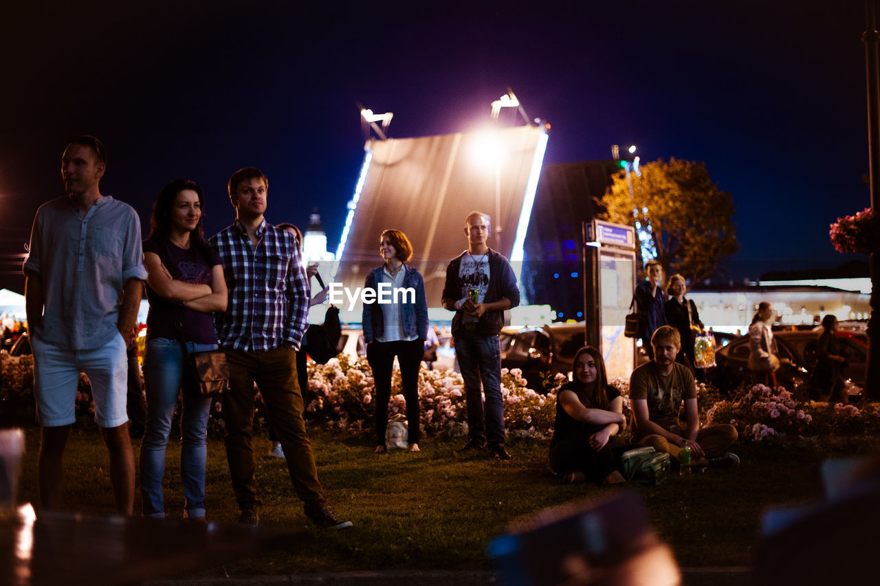 PEOPLE STANDING IN FRONT OF ILLUMINATED FIRE