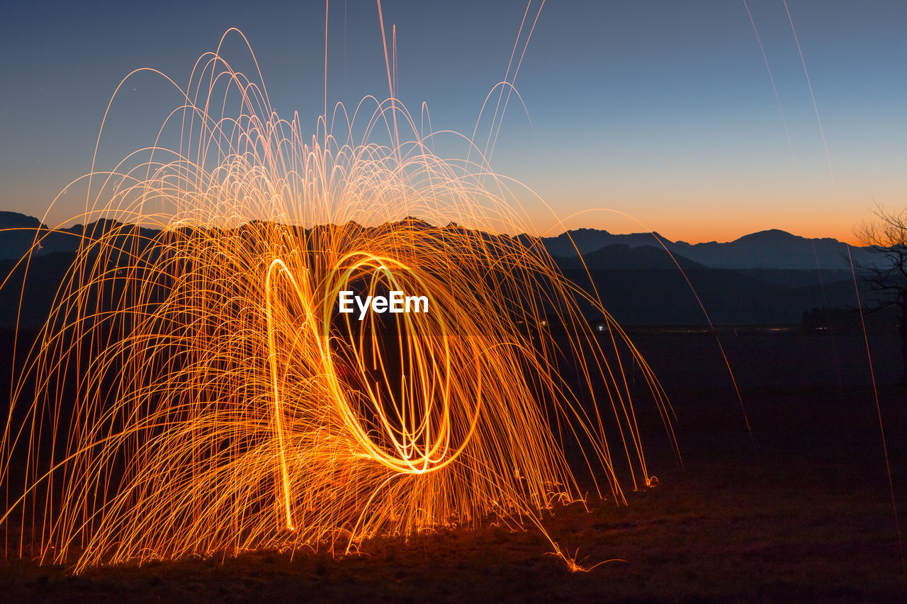 Light Painting With Fire Against Sky At Night