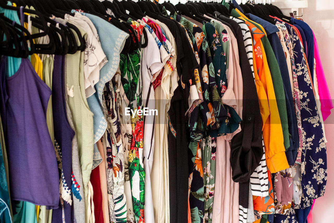 choice, variation, retail, clothing, hanging, multi colored, store, large group of objects, fashion, rack, retail display, clothes rack, shopping, for sale, market, coathanger, in a row, indoors, textile, no people, consumerism, order, sale, garment