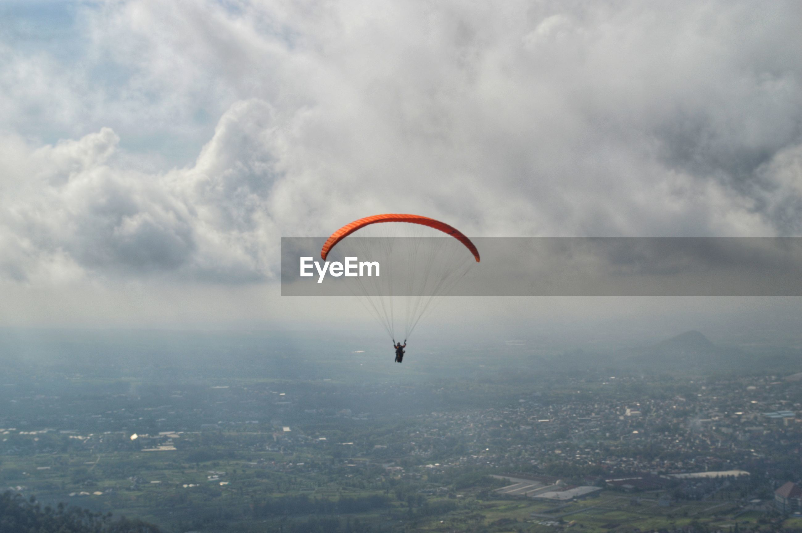 PEOPLE PARAGLIDING OVER CITYSCAPE AGAINST SKY