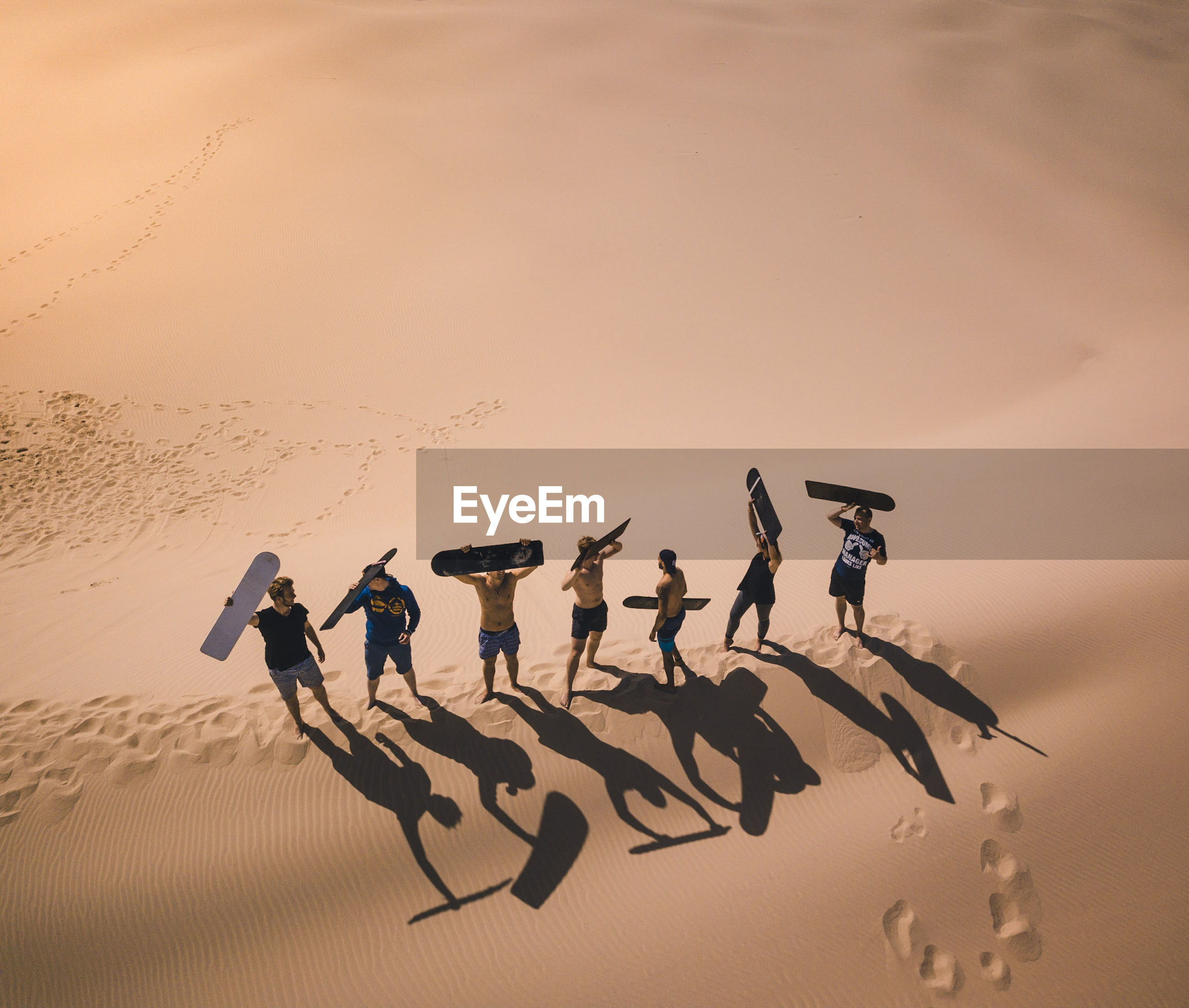High Angle View Of Male Friends Carrying Surfboard While Standing At Beach