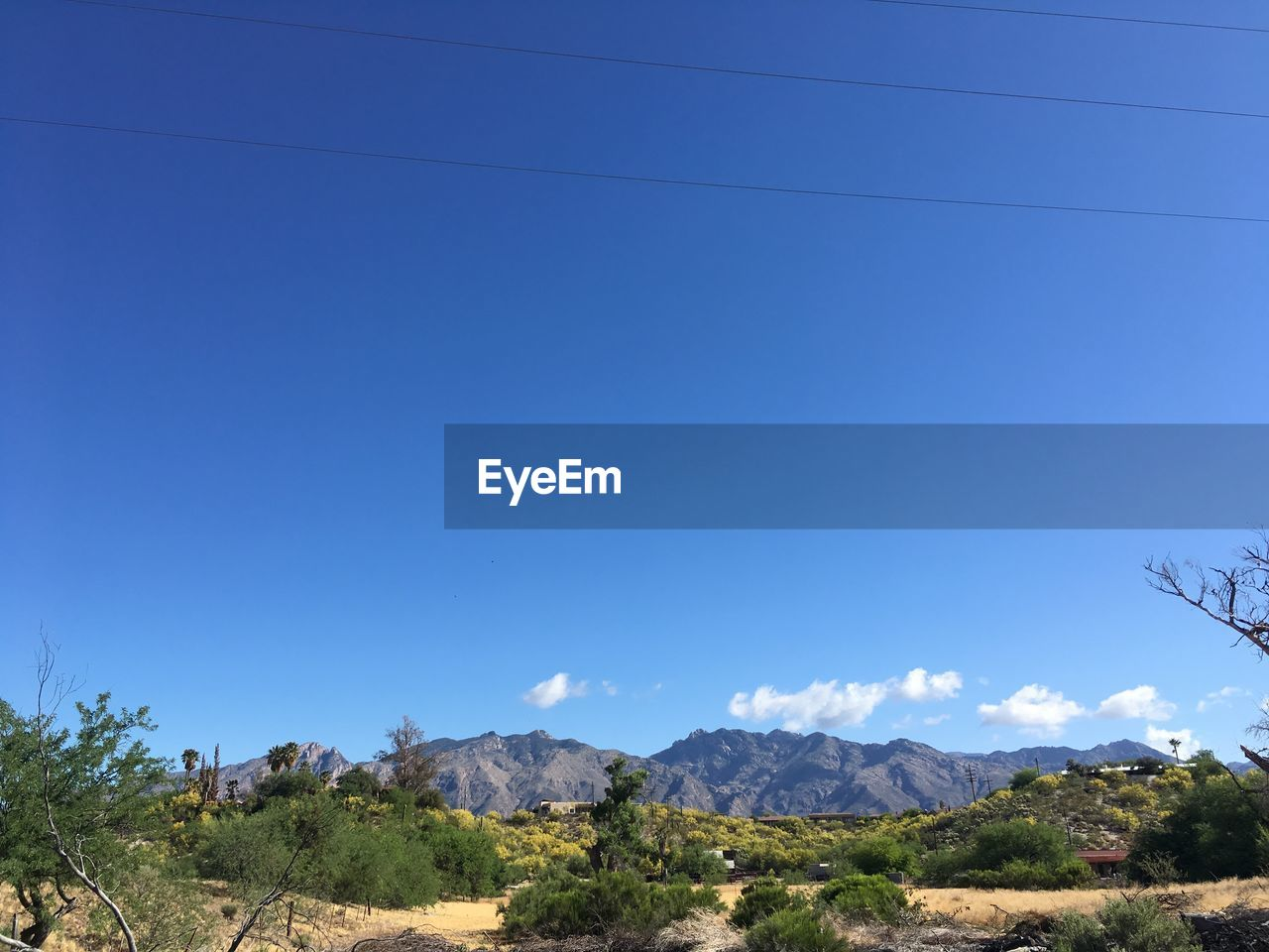 sky, blue, mountain, scenics - nature, tranquility, tranquil scene, beauty in nature, clear sky, nature, plant, no people, tree, copy space, day, environment, landscape, non-urban scene, cable, mountain range, idyllic, outdoors, arid climate
