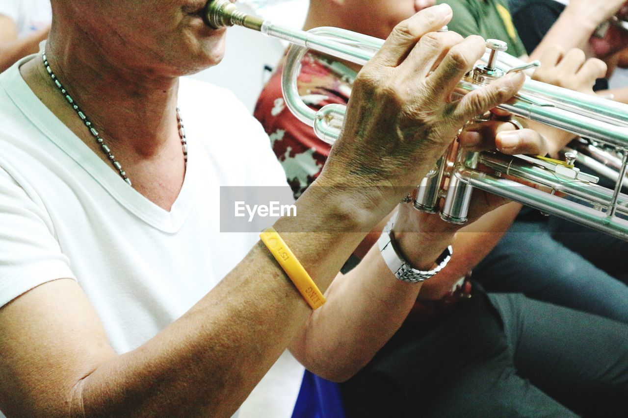human hand, musical instrument, real people, playing, hand, music, holding, men, arts culture and entertainment, people, human body part, midsection, focus on foreground, indoors, lifestyles, two people, casual clothing, brass instrument, day, trumpet, finger