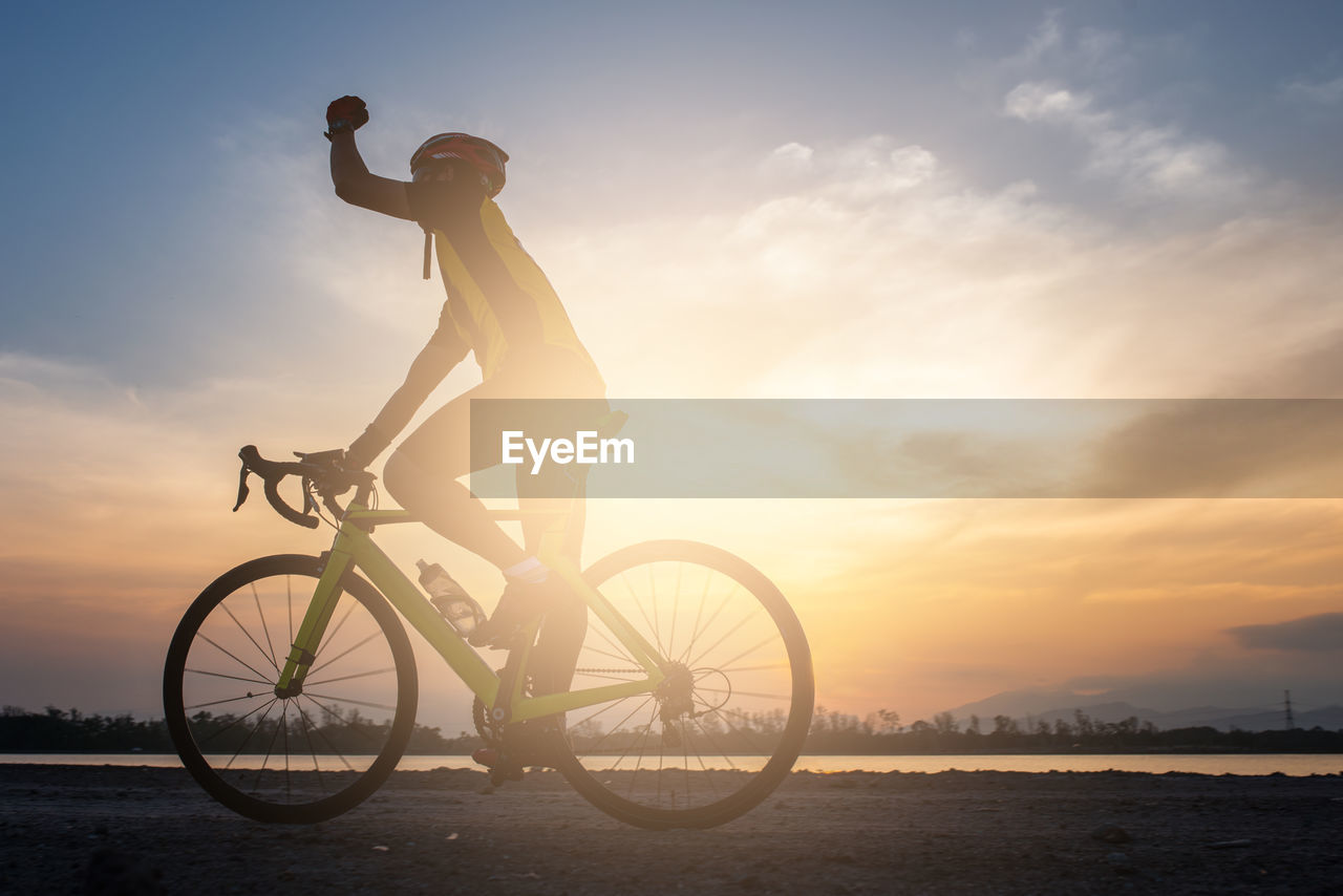 Man riding bicycle on land against sky during sunset