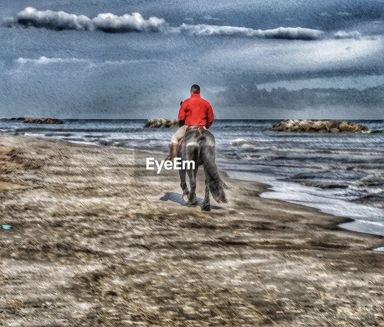 Rear View Of Man Ridding Horse On Beach