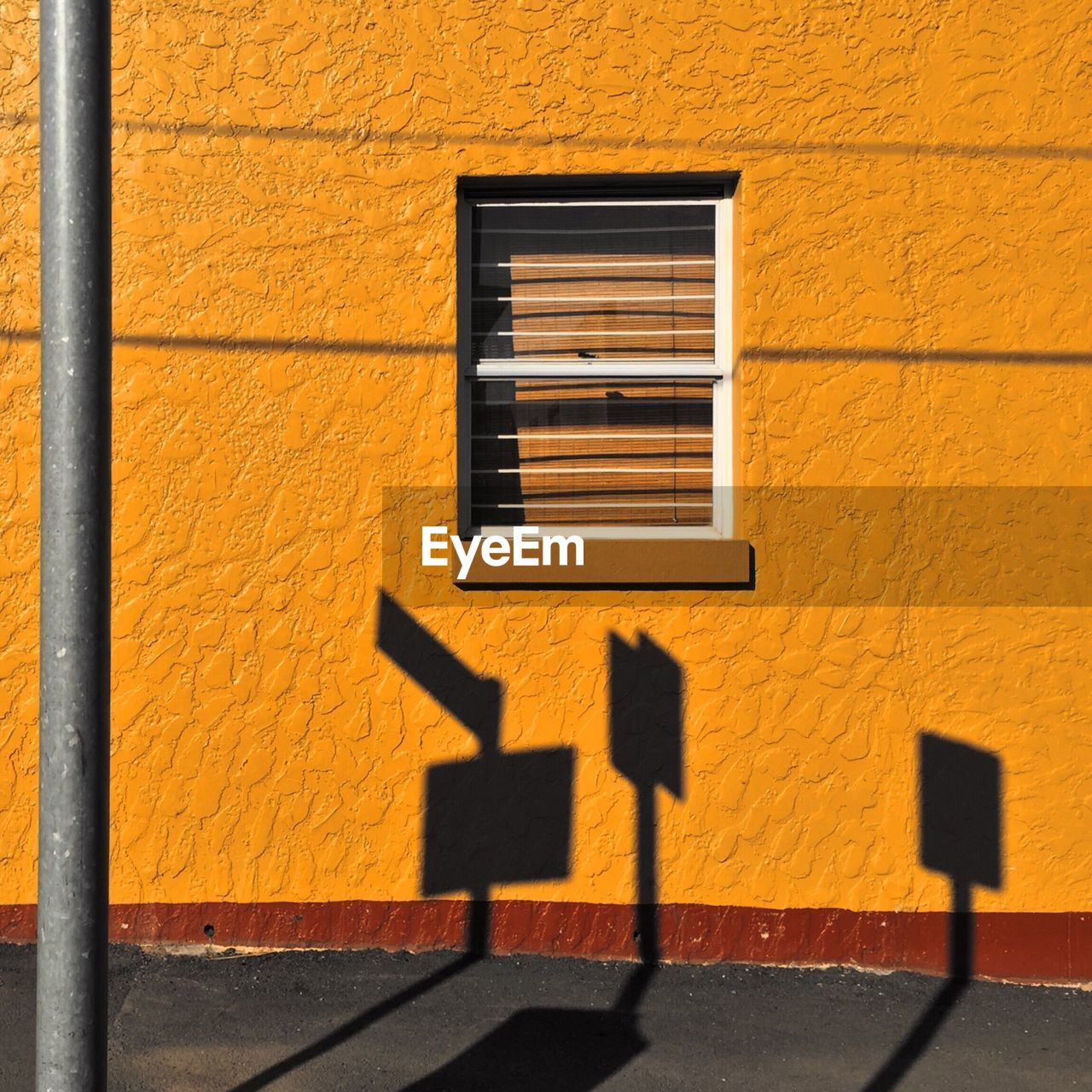 Shadow of signboards on orange wall of building