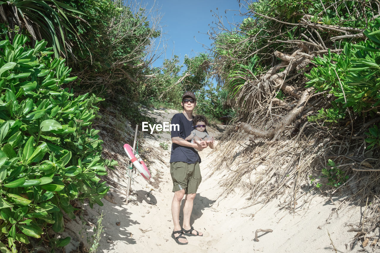Father Carrying Son While Standing At Beach By Plants During Sunny Day