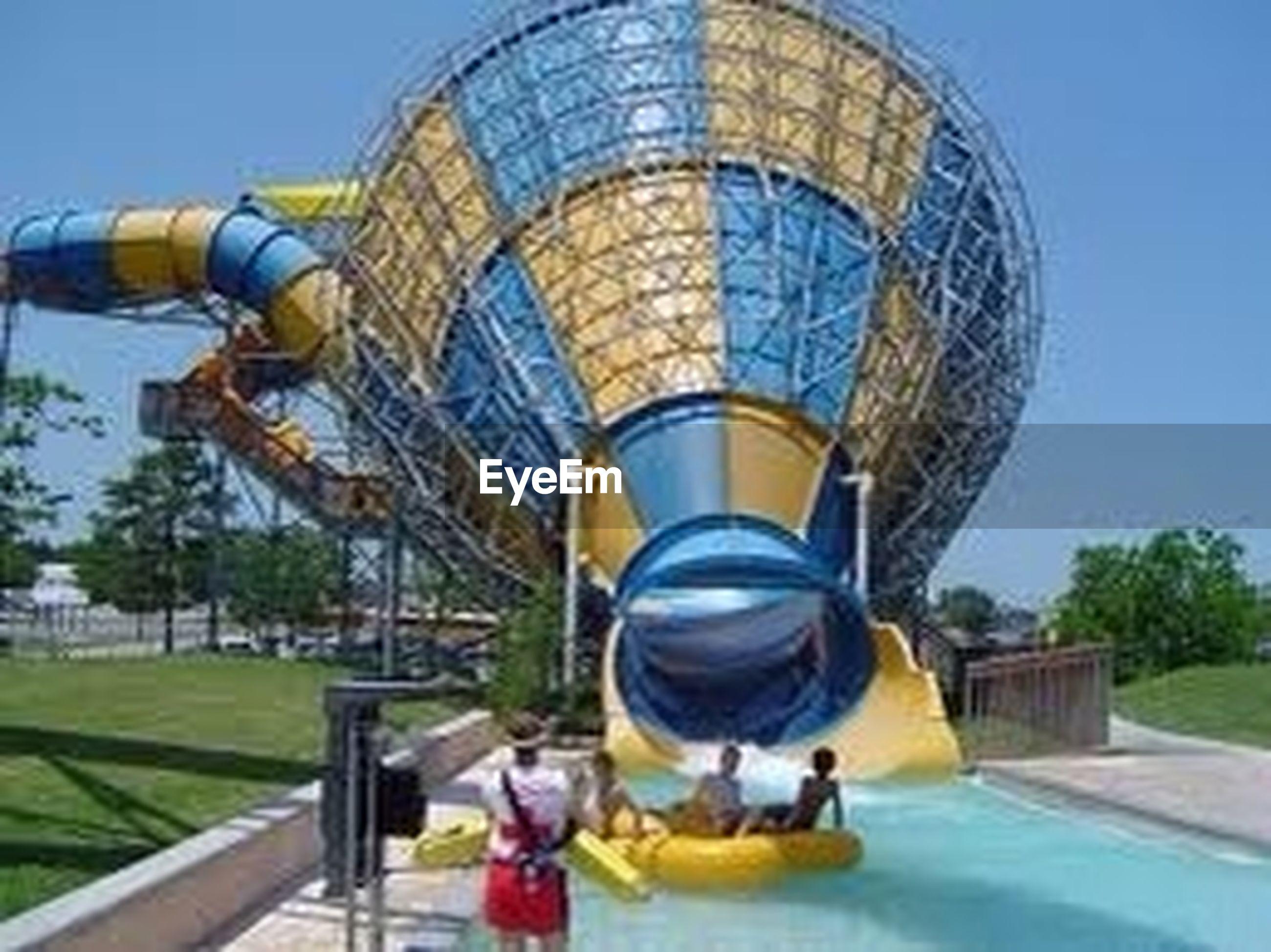 leisure activity, blue, amusement park, lifestyles, clear sky, childhood, amusement park ride, transportation, arts culture and entertainment, built structure, sunlight, sky, travel, architecture, fun, men, ferris wheel, outdoors