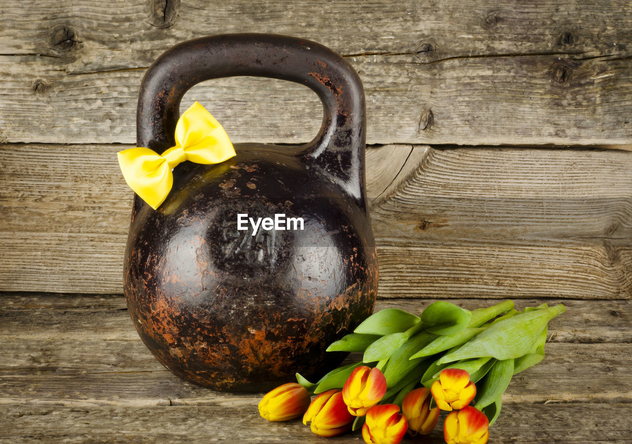 Close-Up Of Kettlebell With Tulips On Wooden Table