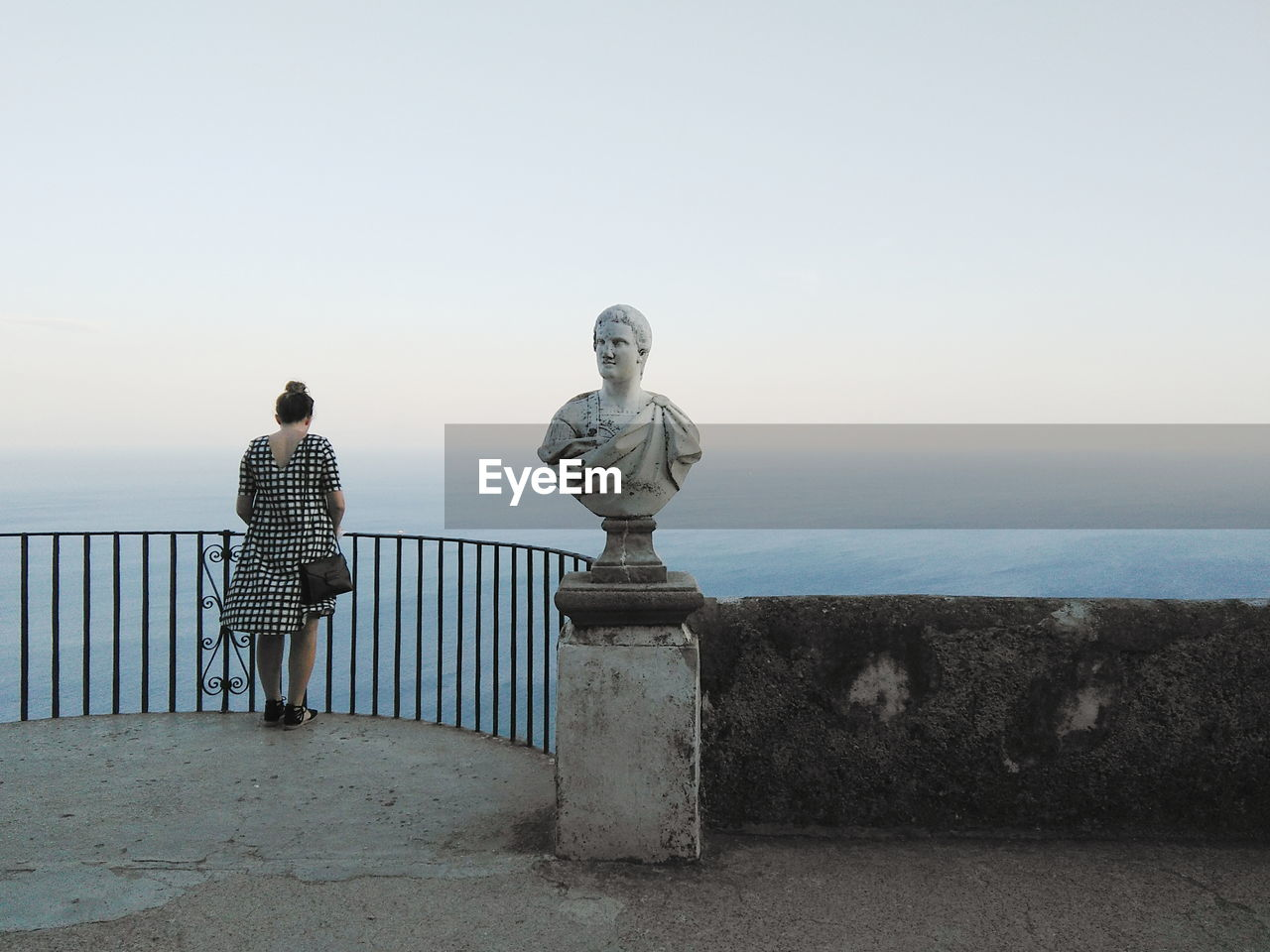 Statue By Woman Standing On Observation Point By Sea