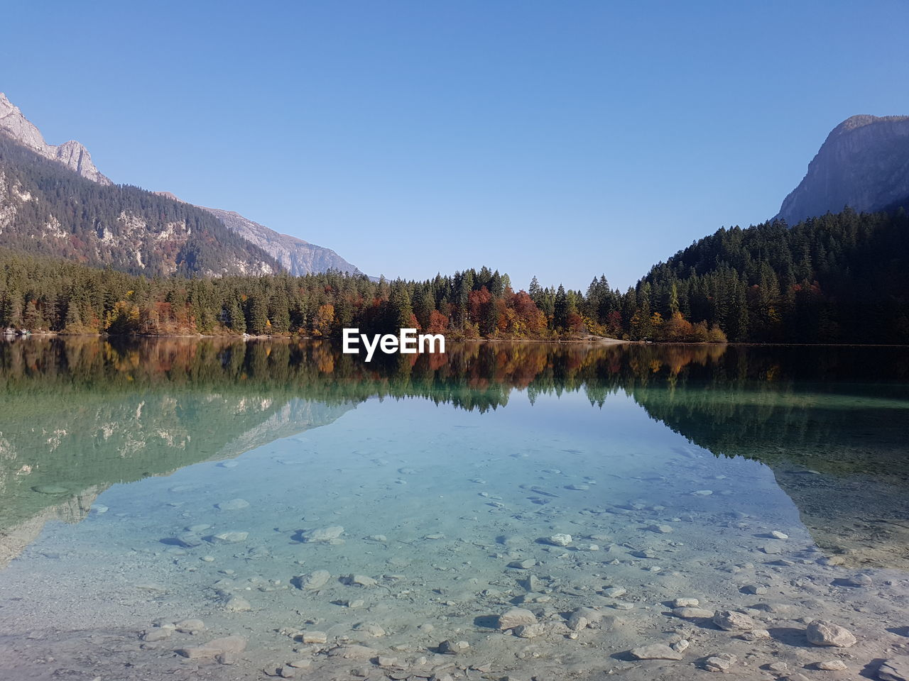 Scenic View Of Lake By Mountain Against Clear Sky