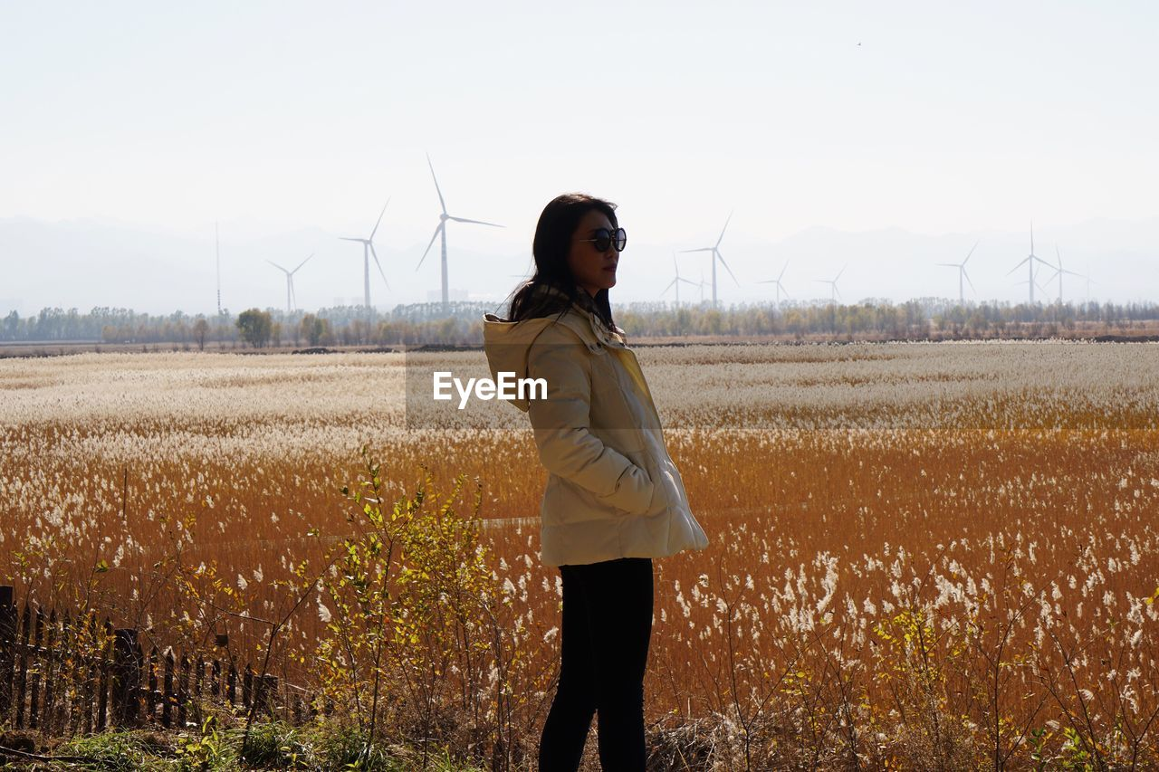 alternative energy, real people, field, wind turbine, one person, wind power, fuel and power generation, environmental conservation, renewable energy, standing, windmill, casual clothing, young women, lifestyles, young adult, leisure activity, nature, outdoors, day, agriculture, rural scene, sky, technology, growth, landscape, industrial windmill, beauty in nature, people
