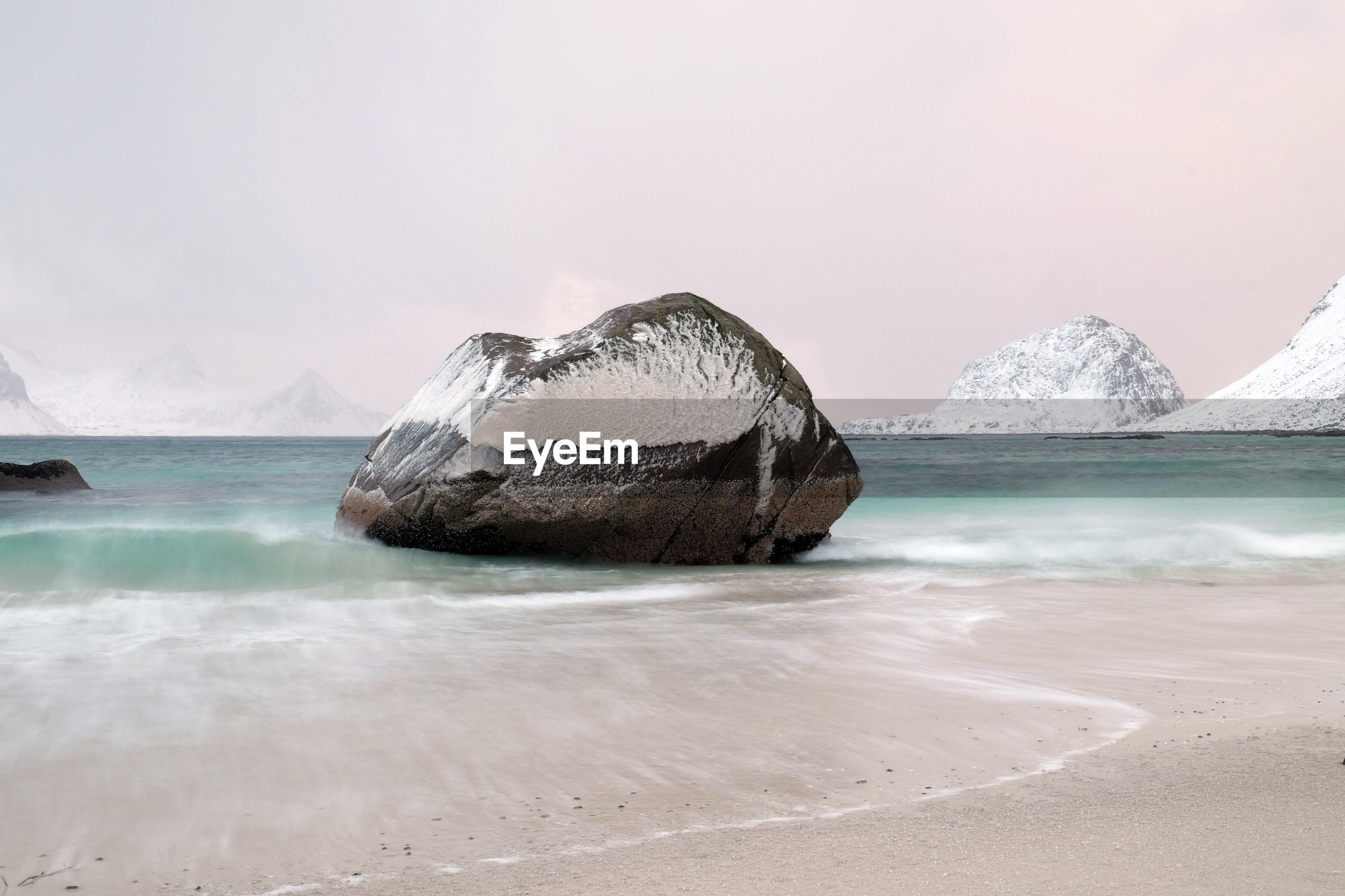 Frozen rock over sea against sky