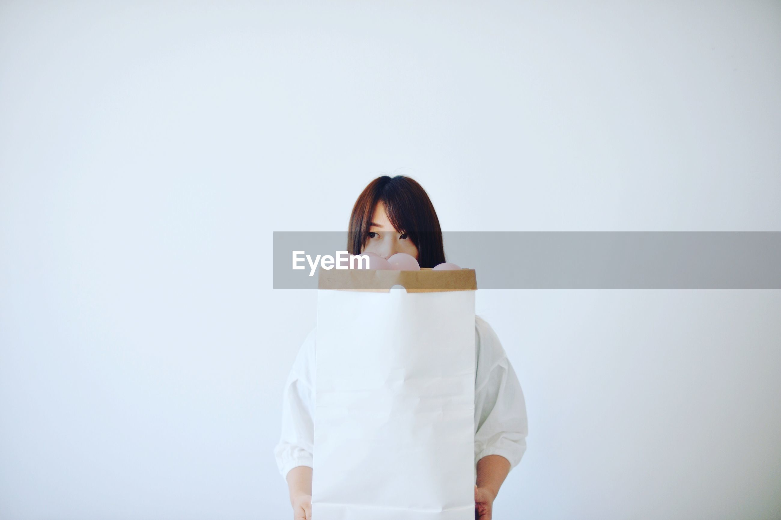 Woman holding paper bag while standing against white background