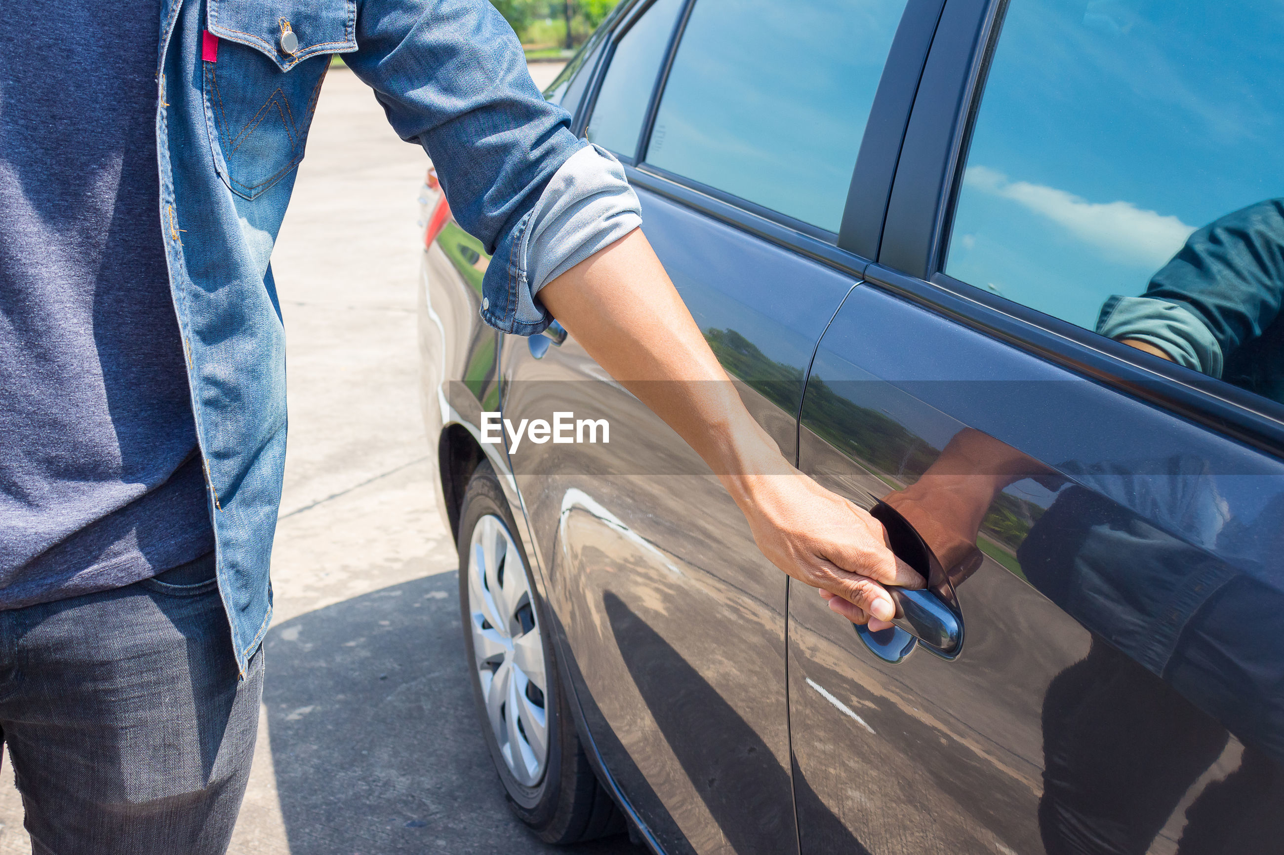 Midsection of man holding car door