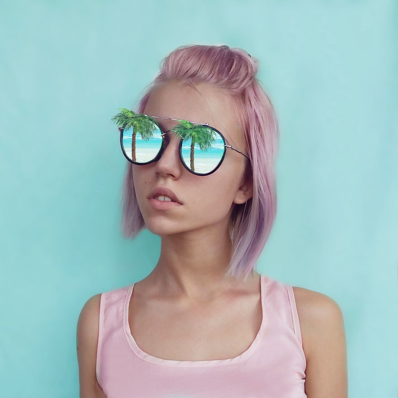 Close-up of young woman wearing sunglasses against blue background