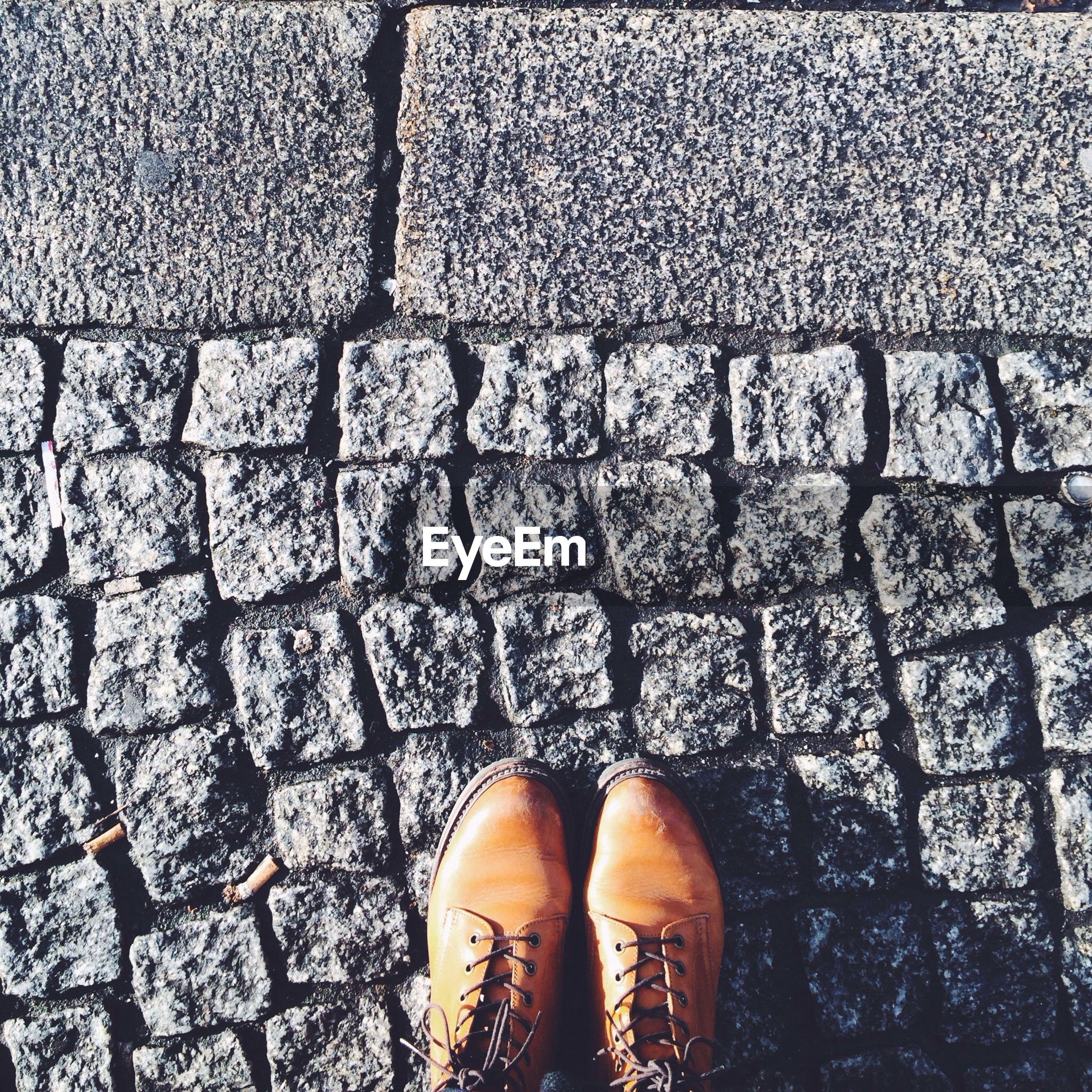 Low section man standing cobblestone street