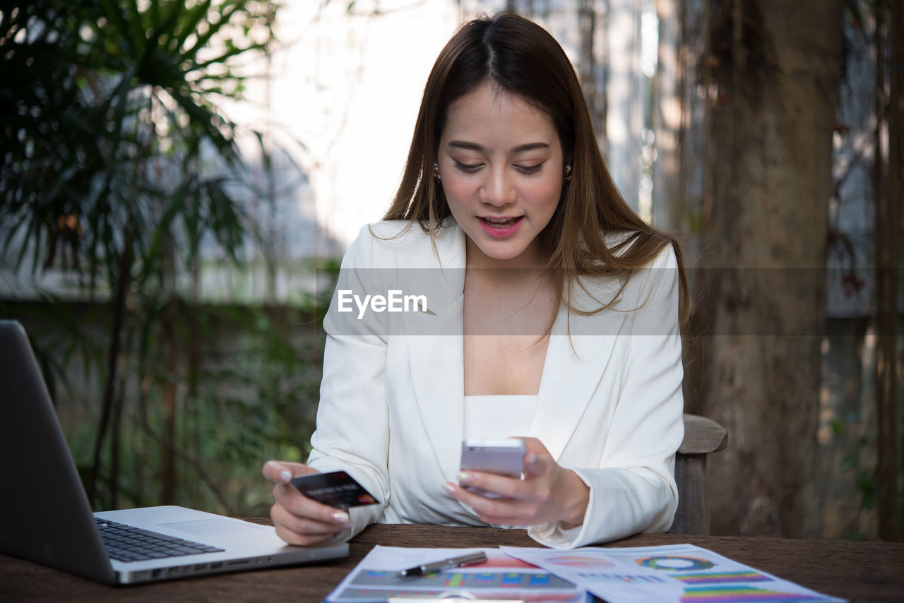 Young woman using mobile phone while holding credit card at table