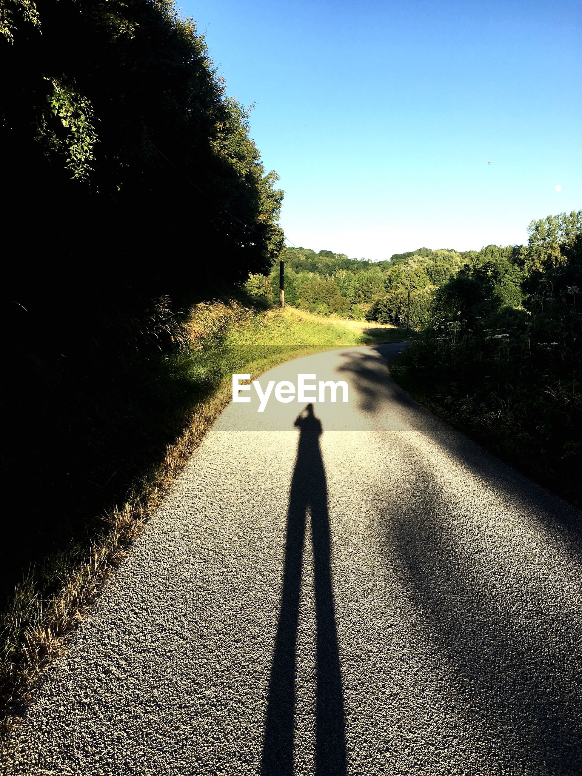 Shadow of person walking on road