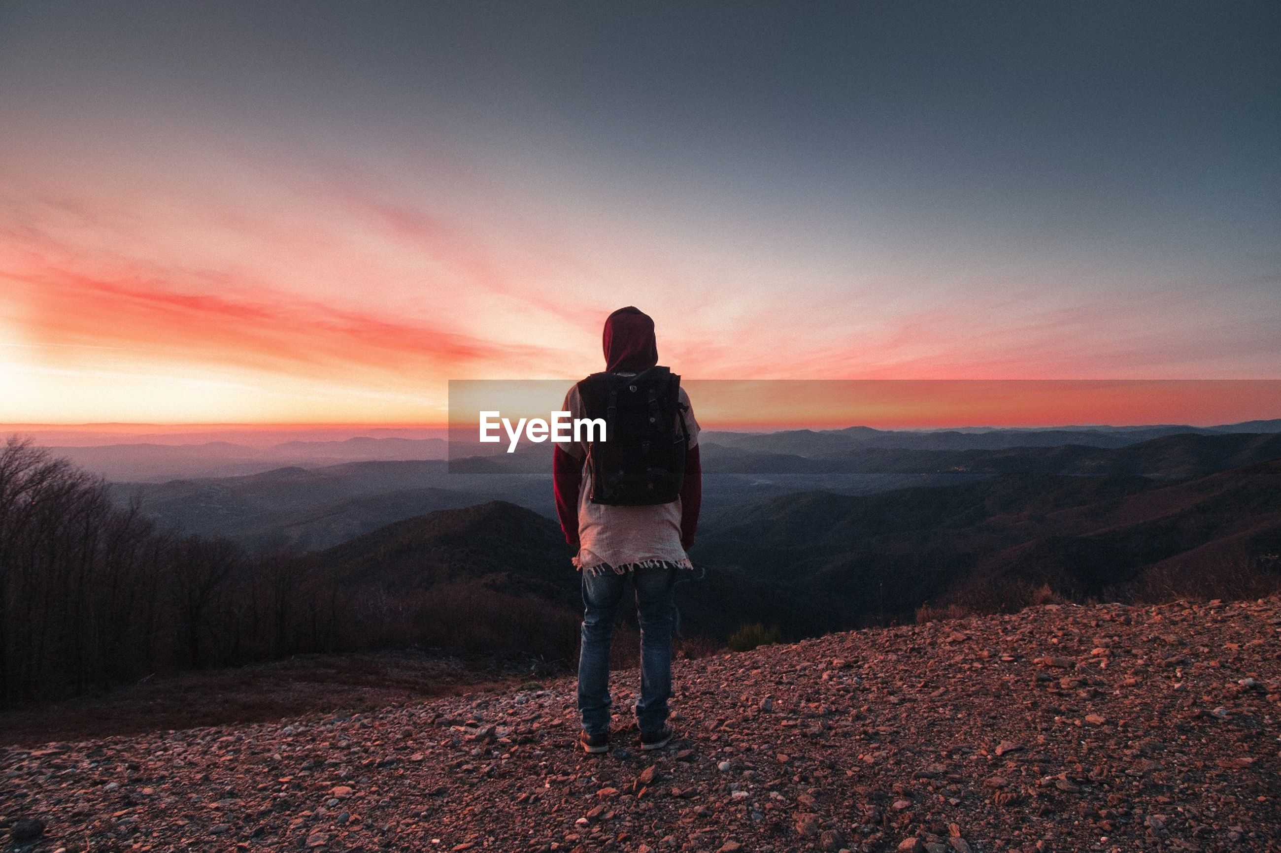 Rear view full length of man looking at mountains during sunset