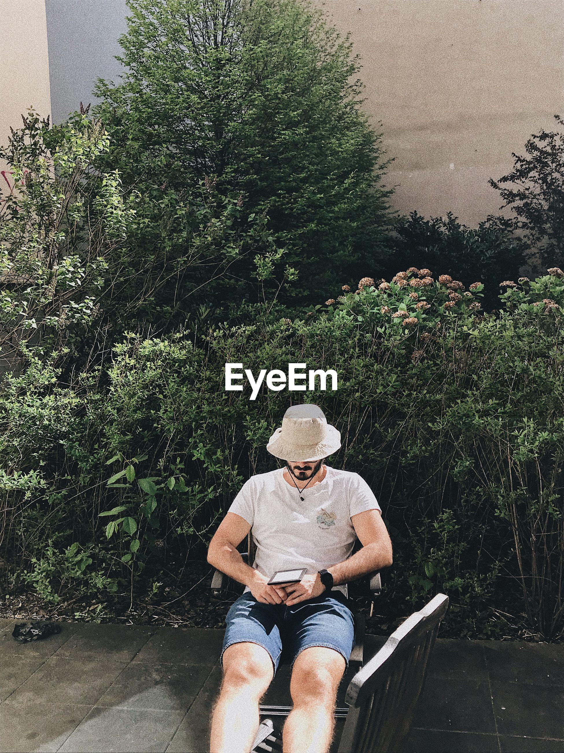 Man reading against trees
