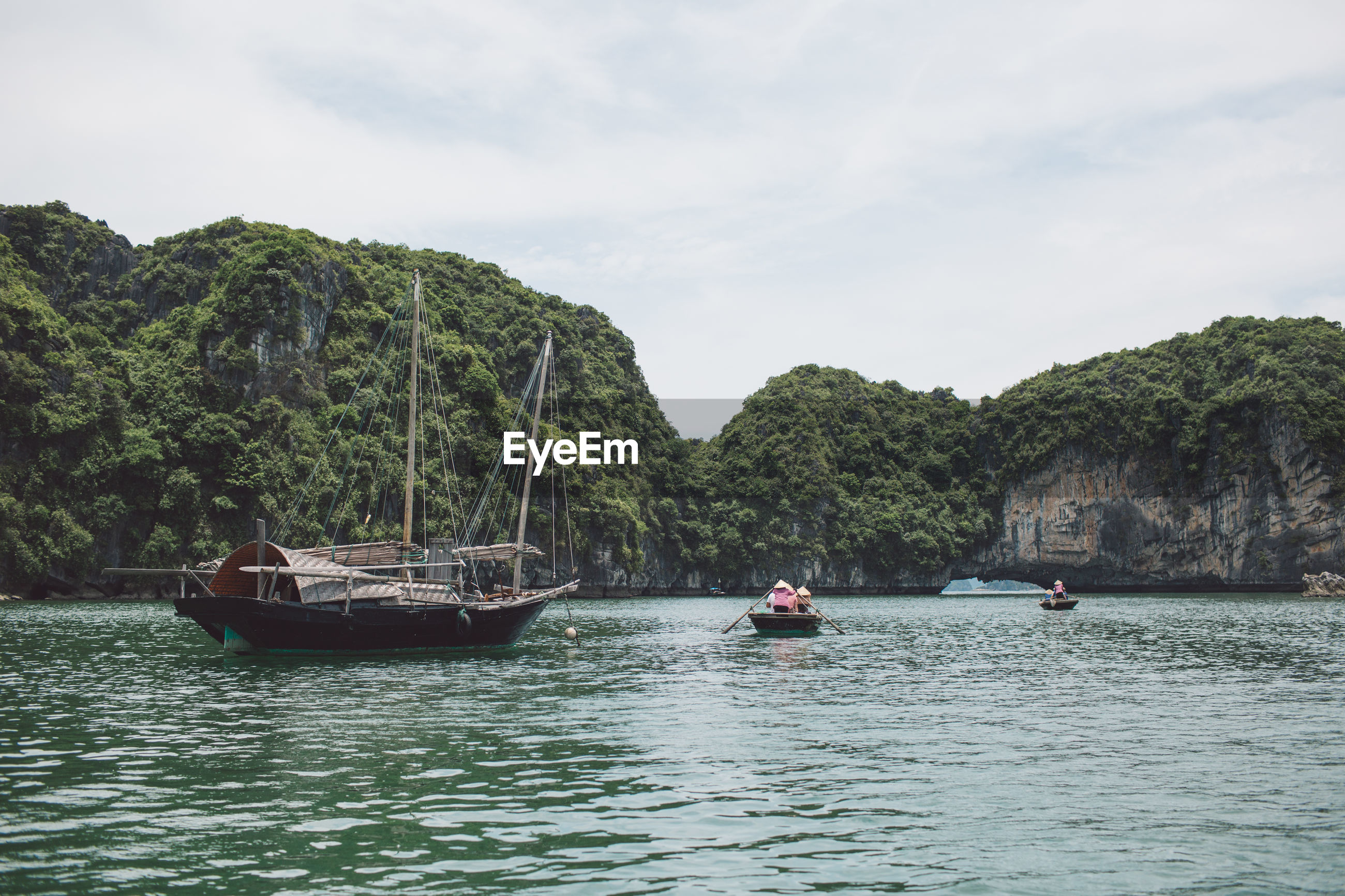 Fishing boat on halong bay by mountains