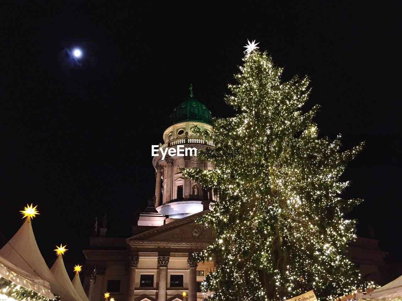 Low angle view of illuminated christmas tree outside neue kirche against sky