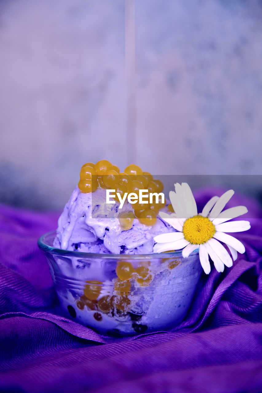 Close-Up Of Dessert With Caviar And White Daisy In Bowl On Table