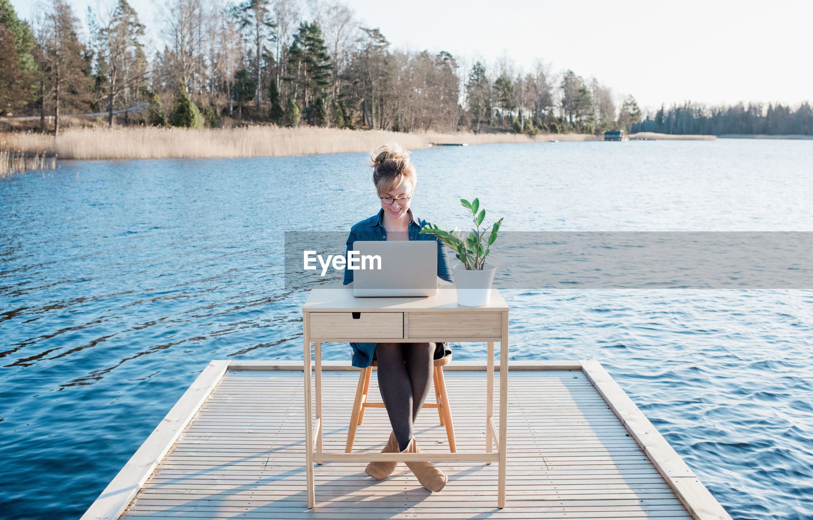 WOMAN SITTING ON TABLE AT SEASIDE