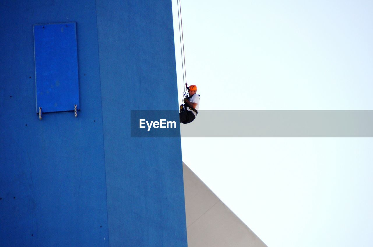 architecture, built structure, building exterior, blue, day, real people, occupation, low angle view, one person, copy space, men, sky, building, clear sky, nature, working, warning sign, risk, outdoors