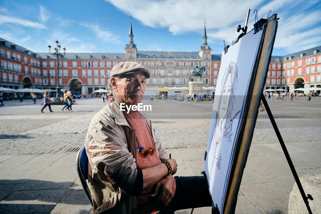FULL LENGTH OF MAN SITTING AT PARK AGAINST SKY