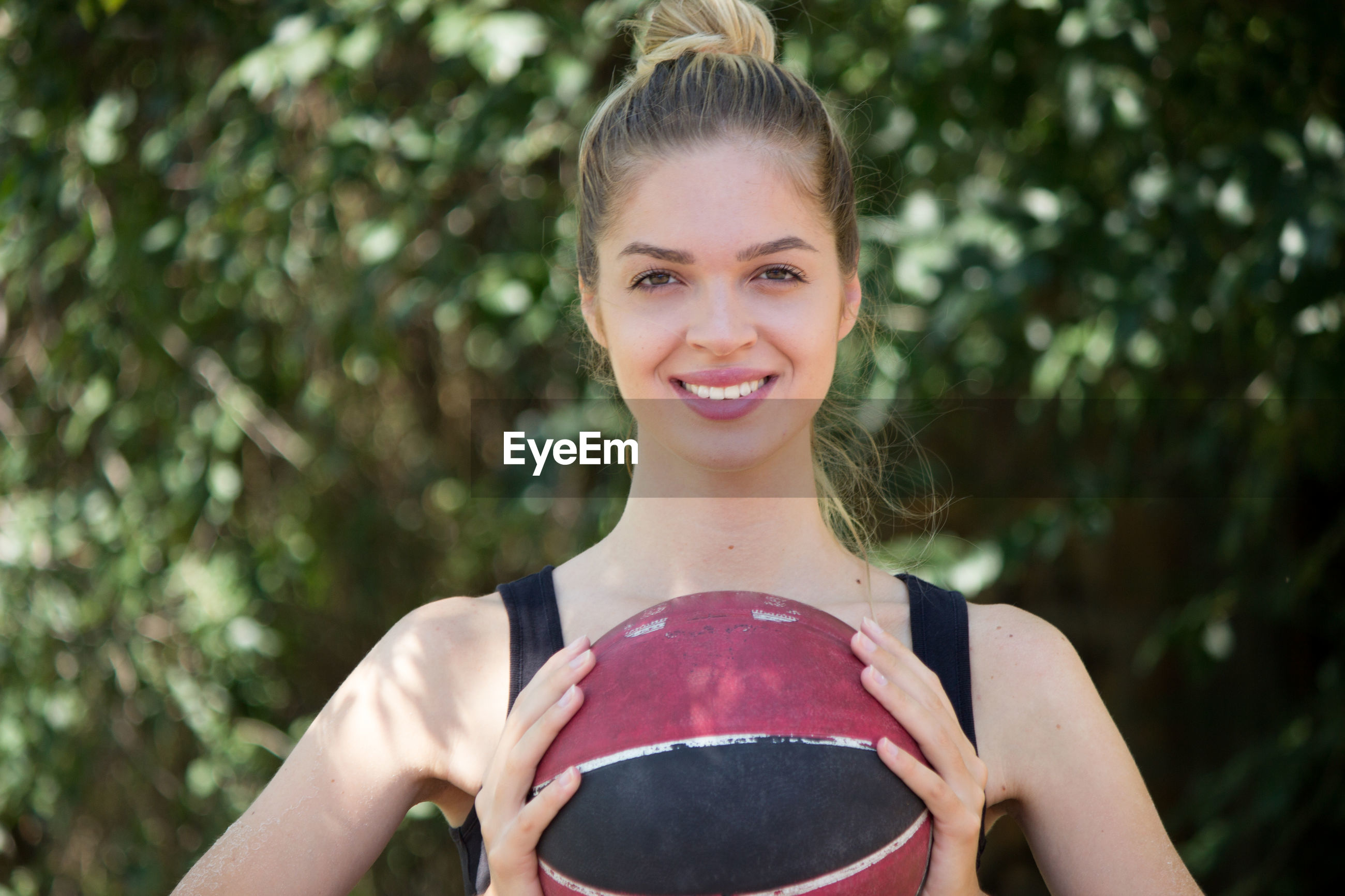 Portrait of young woman holding basketball in park