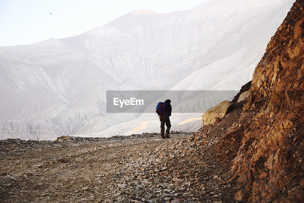 REAR VIEW OF PEOPLE ON MOUNTAIN
