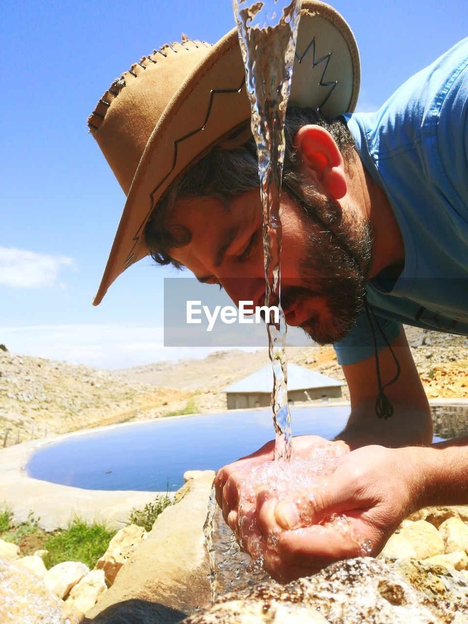 Close-up of man drinking water against sky