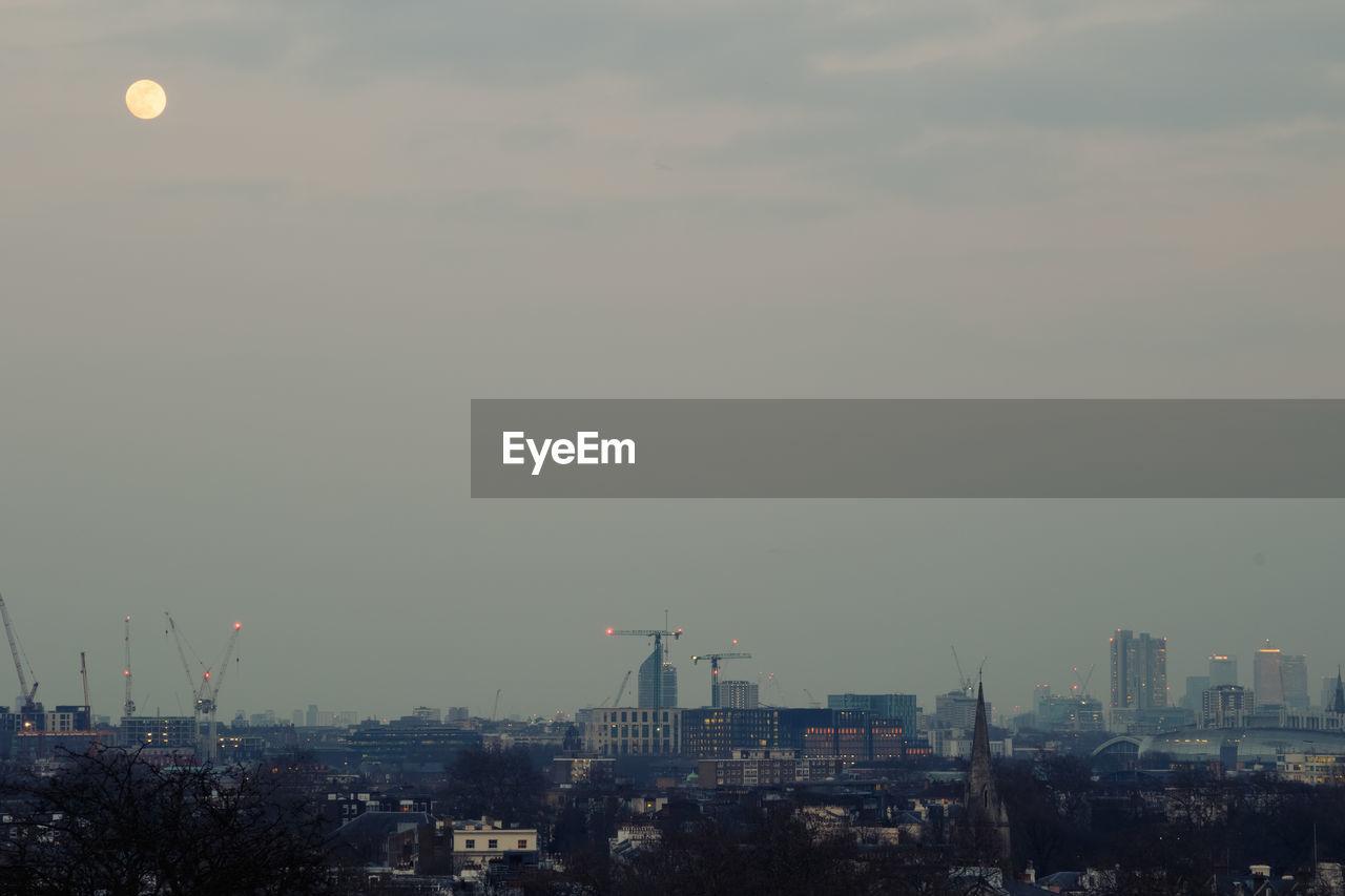 AERIAL VIEW OF BUILDINGS AGAINST SKY AT DUSK