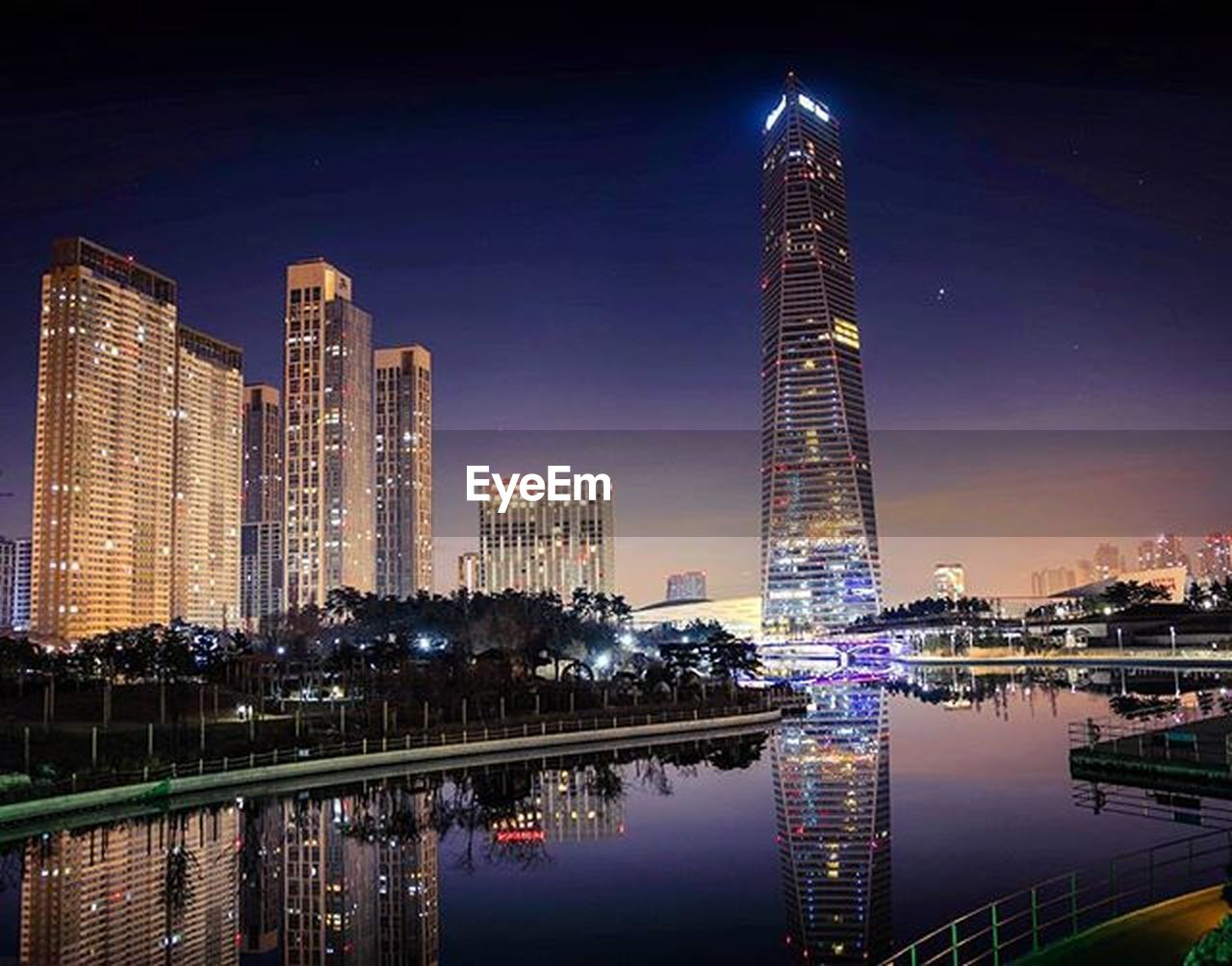 skyscraper, night, illuminated, architecture, modern, city, urban skyline, reflection, tower, cityscape, building exterior, sky, built structure, travel destinations, business finance and industry, downtown district, water, travel, river, waterfront, no people, multi colored, outdoors, futuristic