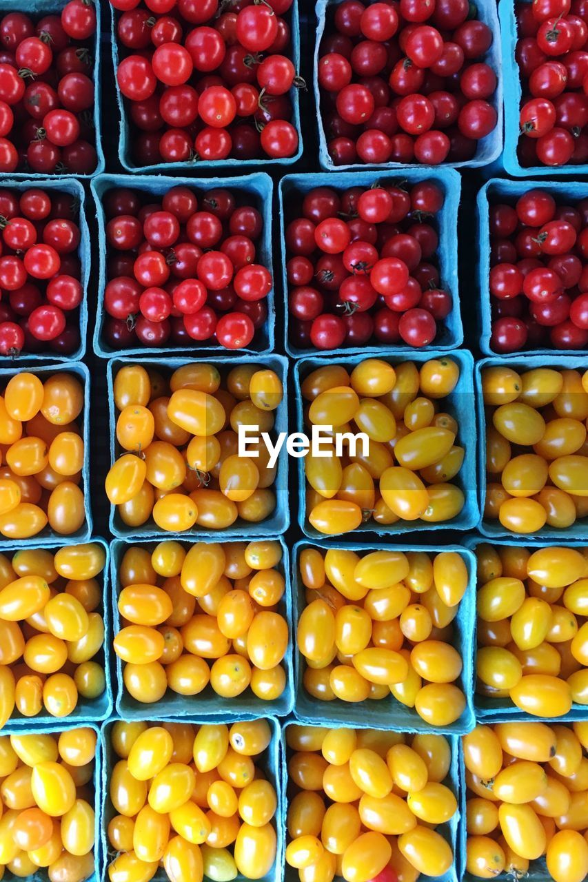Full frame shot of yellow and red tomatoes in boxes for sale