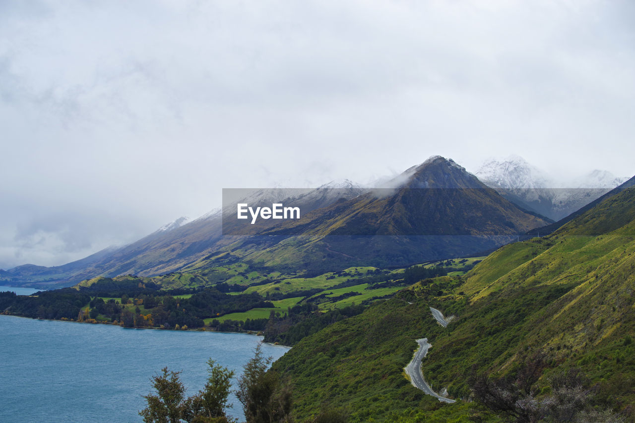 Scenic View Of Mountains By Lake Against Cloudy Sky