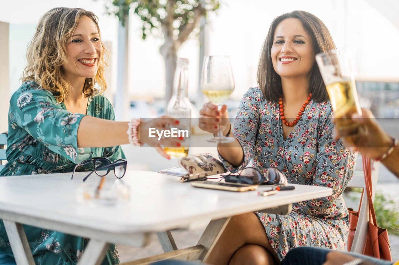 Smiling Friends Toasting Alcoholic Drinks At Restaurant