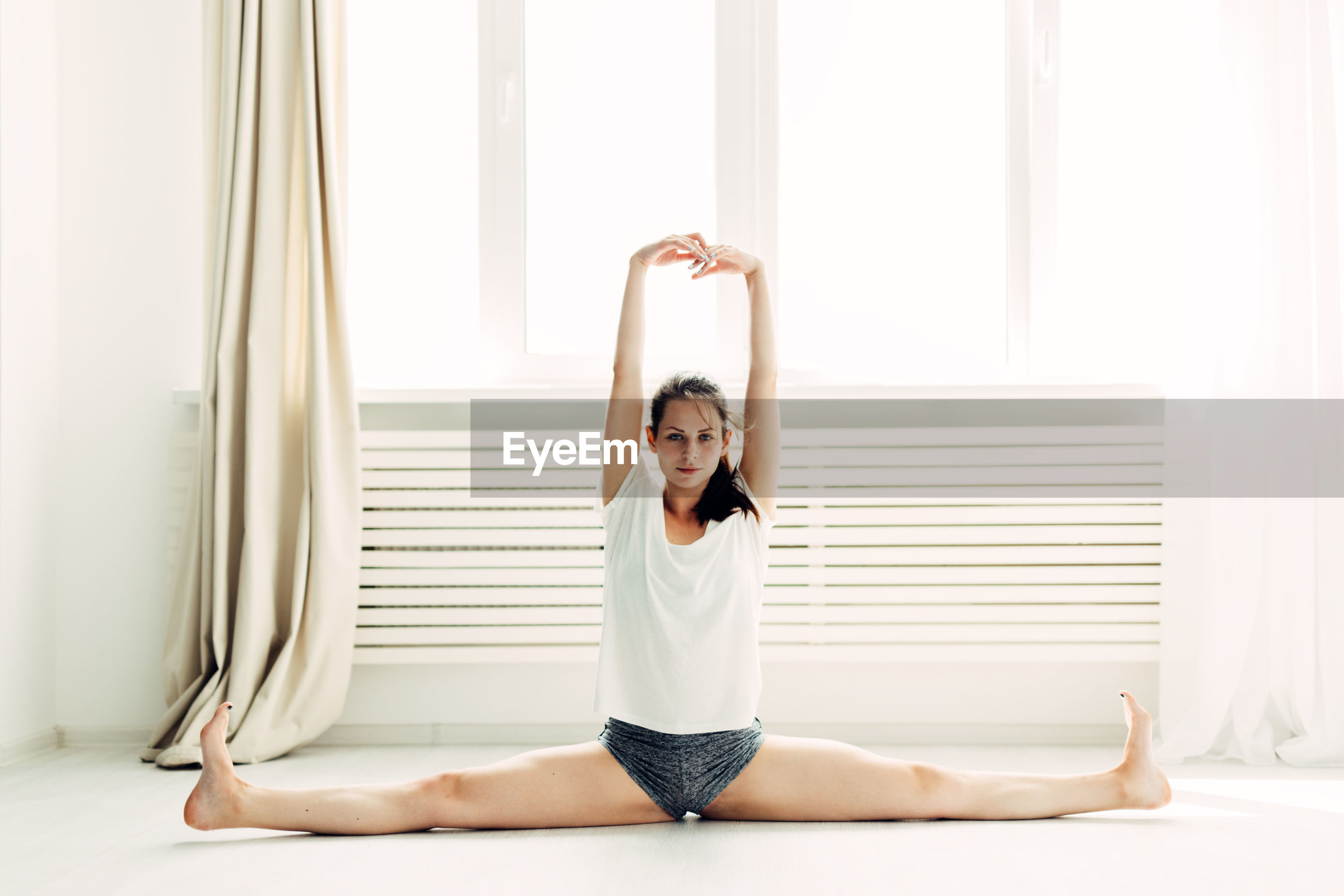 Full length portrait of young woman doing the splits while practicing yoga at home