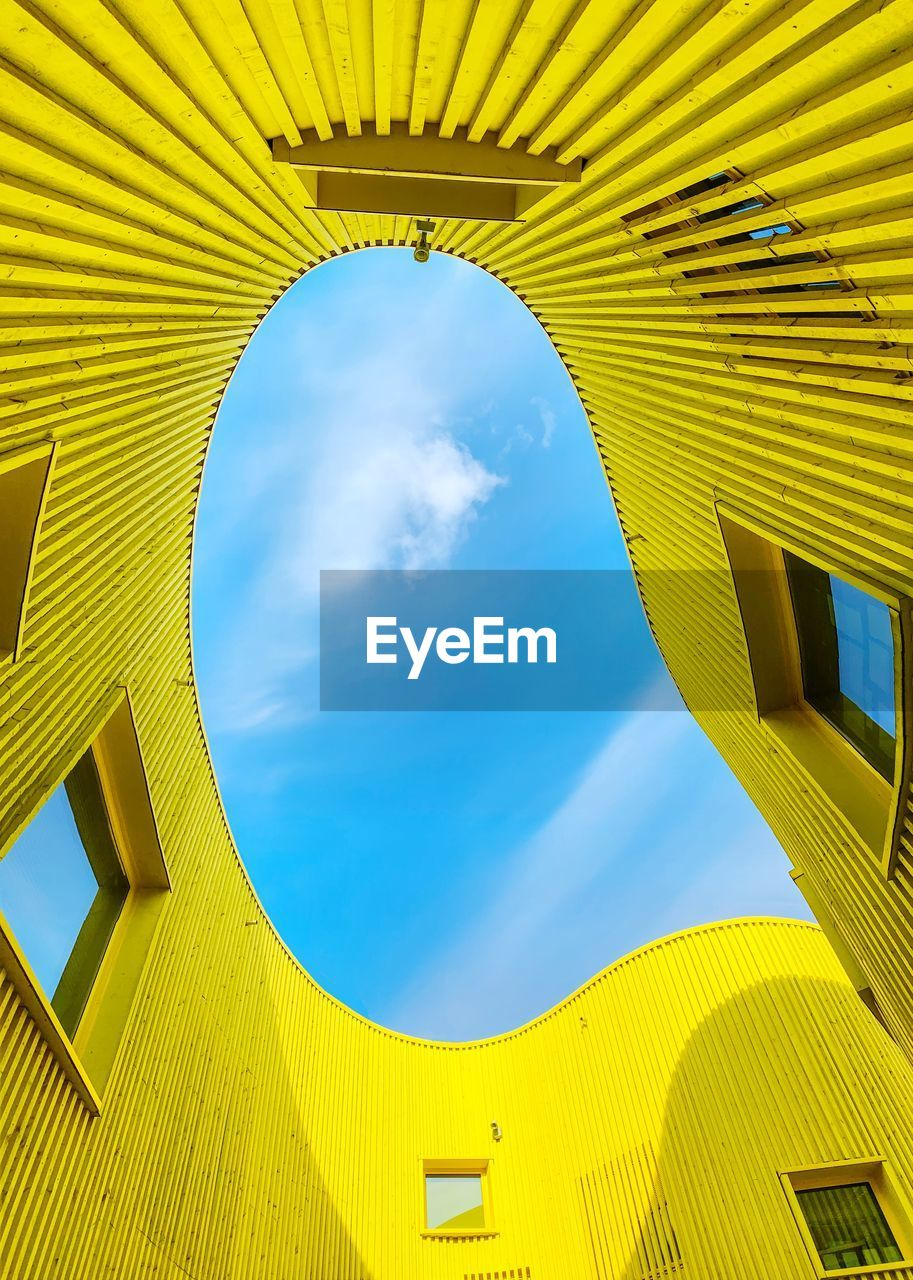 sky, built structure, architecture, yellow, low angle view, cloud - sky, building exterior, blue, day, no people, nature, building, sunlight, outdoors, arch, pattern, geometric shape, shape, design, window, light fixture