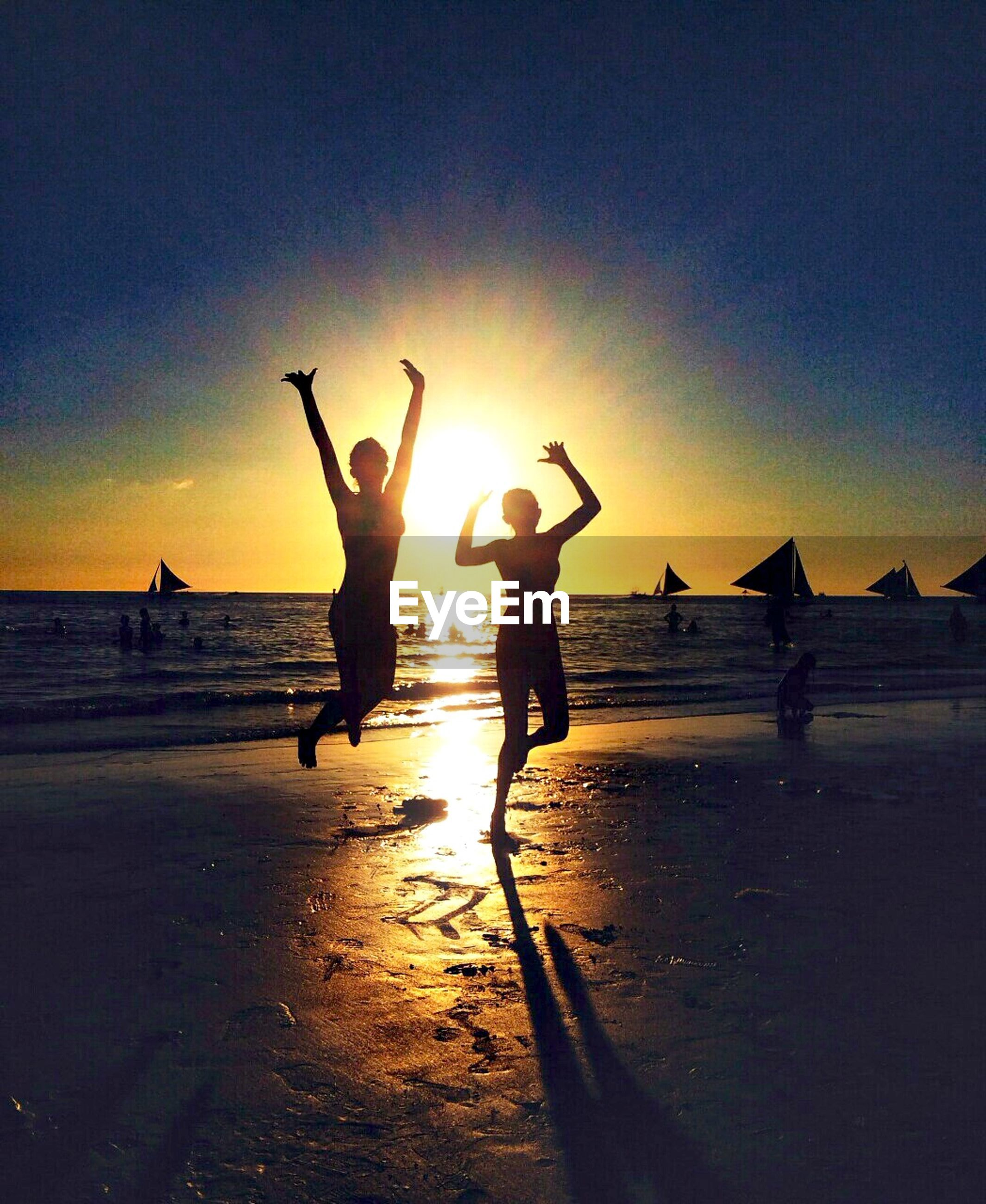 lifestyles, water, leisure activity, silhouette, sunset, beach, sea, reflection, enjoyment, vacations, sun, sky, togetherness, fun, scenics, nature, beauty in nature, flying, tranquility, weekend activities, tourism