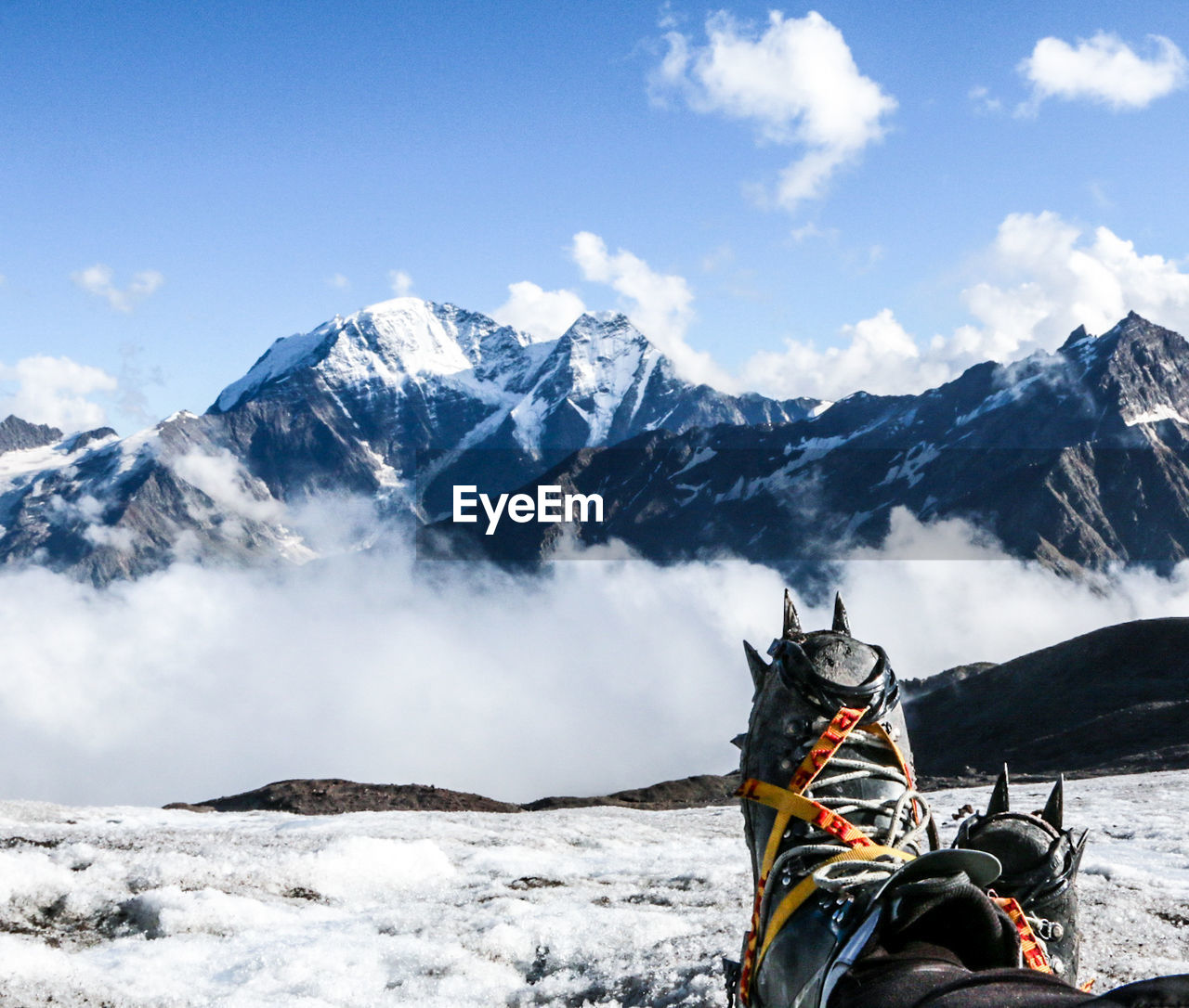 Low Section Of Person Wearing Snow Boot On Snow Covered Field By Mountains Against Sky