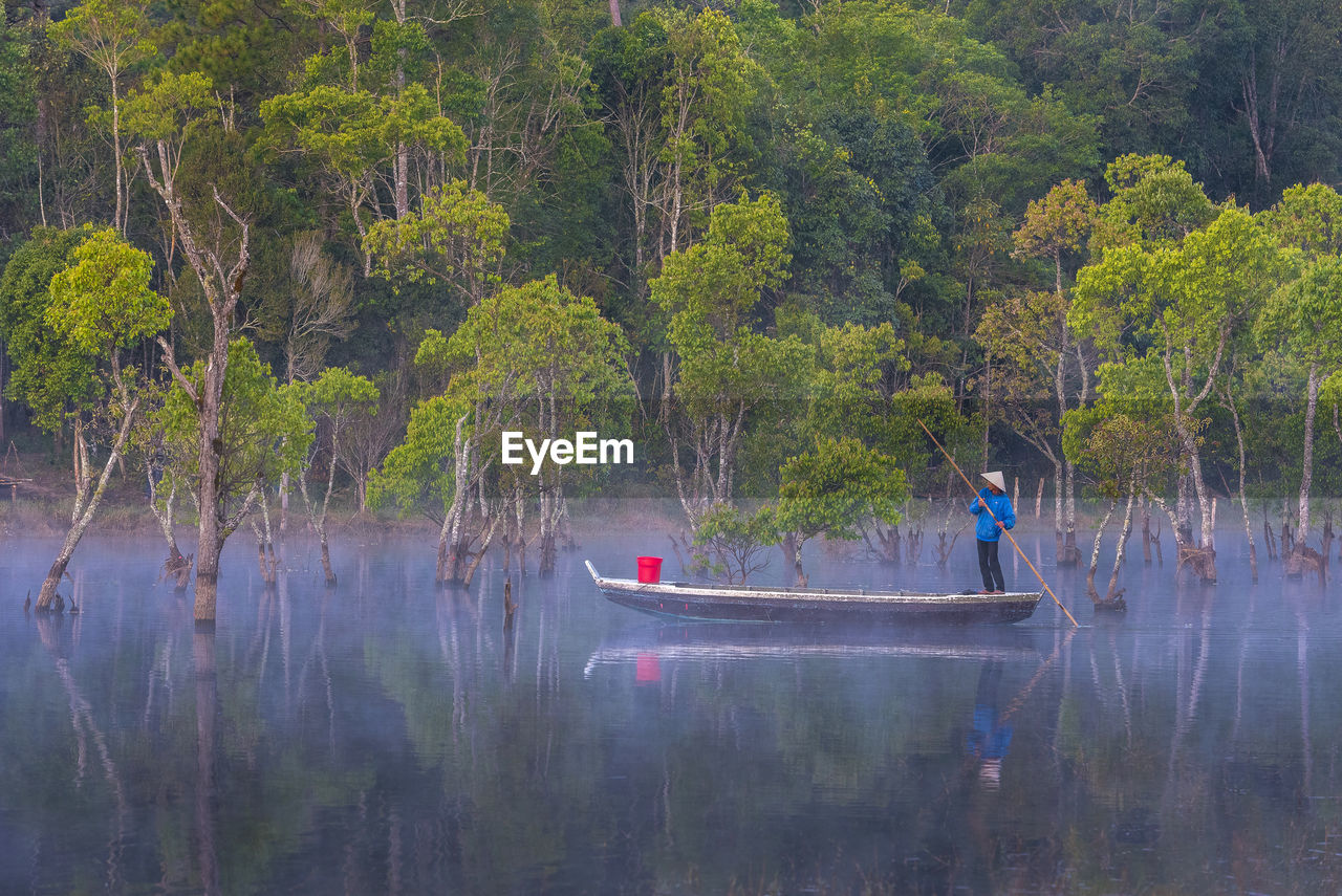 PEOPLE IN BOAT BY TREES IN FOREST