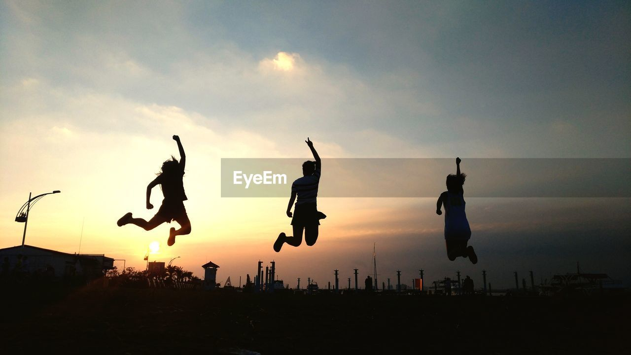 sky, sunset, silhouette, jumping, mid-air, cloud - sky, nature, orange color, leisure activity, real people, lifestyles, vitality, outdoors, full length, building exterior, motion, people, group of people, beauty in nature, architecture