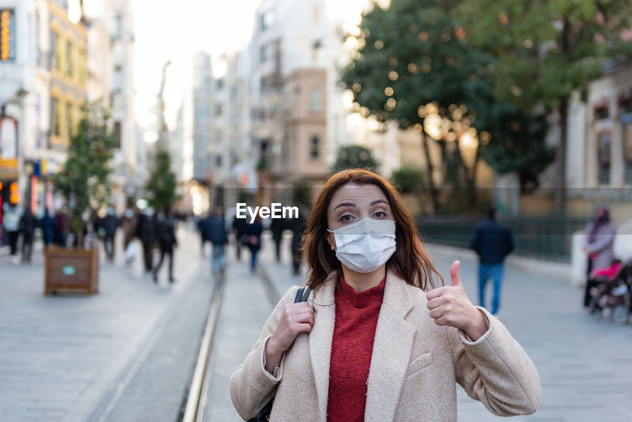 Portrait of woman wearing mask gesturing while standing on city street